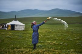 Mongolia, nomad woman making a milk offering